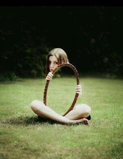 het lijkt alsof je alleen het meisje haar hoofd en benen ziet en dat de rest weg is, maar ze heeft eigenlijk een spiegel vast die de andere kant van het gras spiegelt.