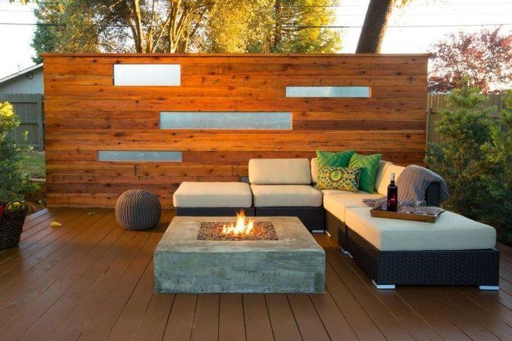 foyer en béton, canapé d'angle en rotin et brise-vue en bois et alu sur la terrasse