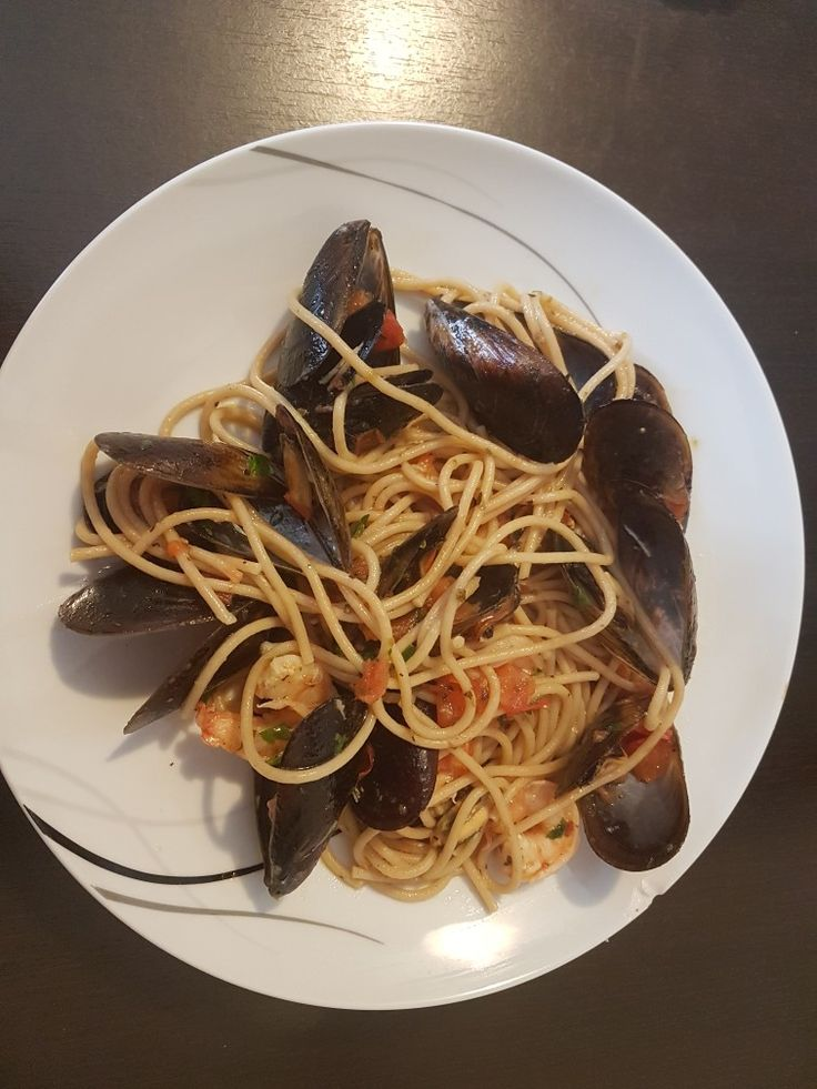 Spaghetti with fresh mussels. Ingredients:spaghetti,fresh mussels,cherry tomatoes,white wine,salt,pepper,2 cloves of garlic and parsley green.