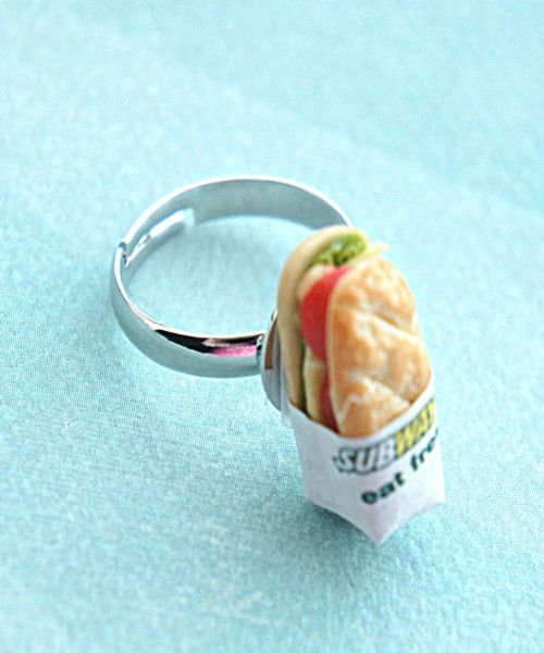 this ring features a handmade sandwich sculpted from polymer clay. it measures about 1.5 cm tall and is securely attached to an adjustable silver tone ring that fits most ring sizes.