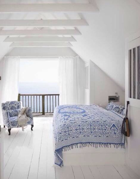 An all white bedroom with blue and white textiles as contrasts