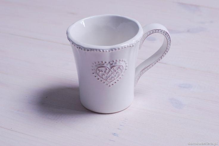 Biały kubek z motywem serca i delikatnymi przetarciami na wypukłościach. Idealny na zimowe wieczory z ciepłą herbatą lub czekoladą. Pomysł na walentynkowy prezent dla dziewczyny.