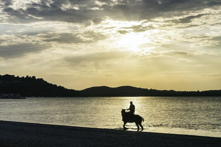 A man is riding a horse in the sea during the late hours of day, as if he is riding in the sunset. A photo taken at the town of Vonitsa, in western Greece.