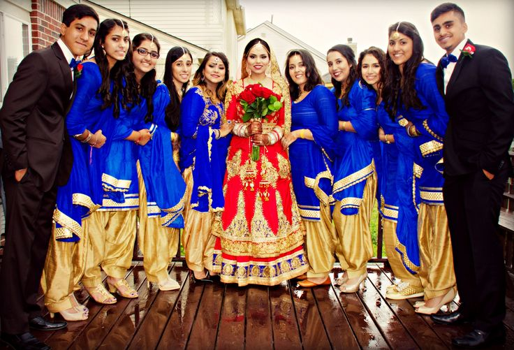 Indian Sikh Punjabi bride with bridesmaids in royal blue suits bridesmen. Wedding