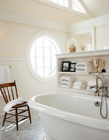 """Designer Clipper Joseph calls the master bathroom his """"ballroom bathroom"""" because of its large size. The large circular window brings a lot of natural light, offering a cheerful feel to the room. The built-in shelves create convenient storage for towels above the Kohler vintage tub."""