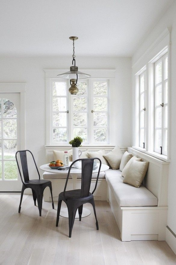 Breakfast nook with large white windows, white table, black chairs, and a built-in bench