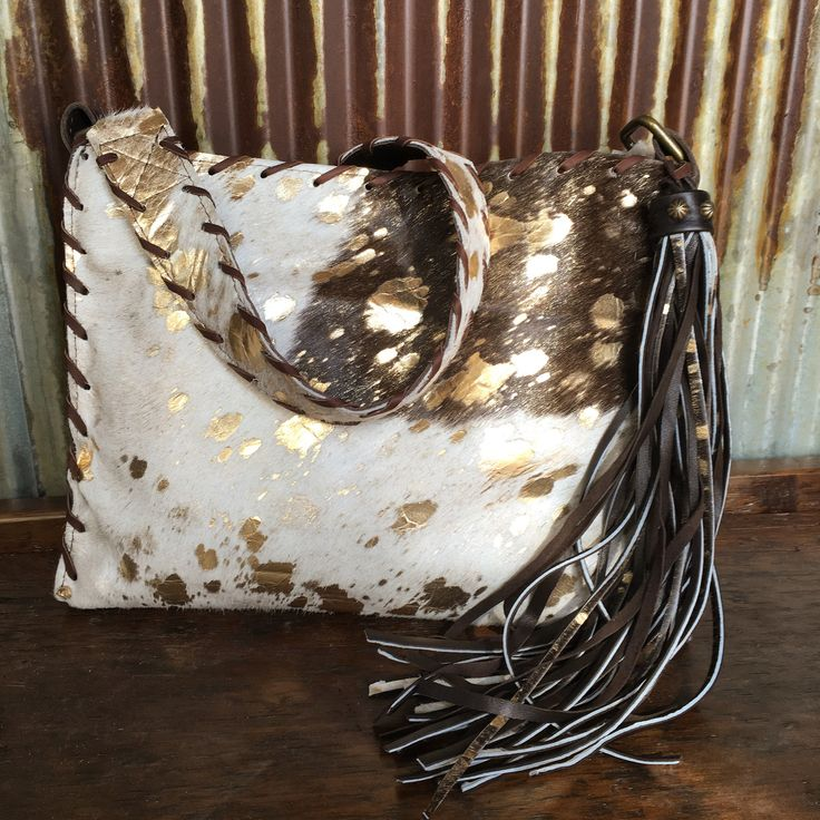 Corriente cowhide purse Acid washed gold leather throughout Leather and hide fringe tassel with brass stud detail Leather lace trim border and shoulder strap Sm