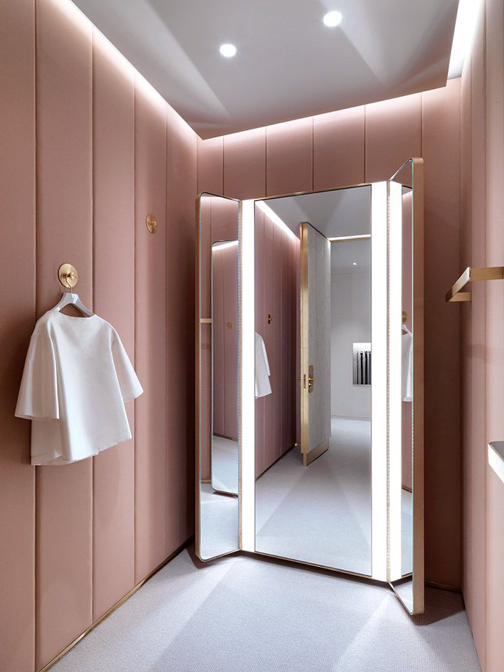 A fitting room clad with dusty pink panelling has an ethereal feel