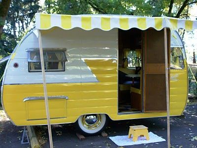 bright yellow vintage trailer with awning.