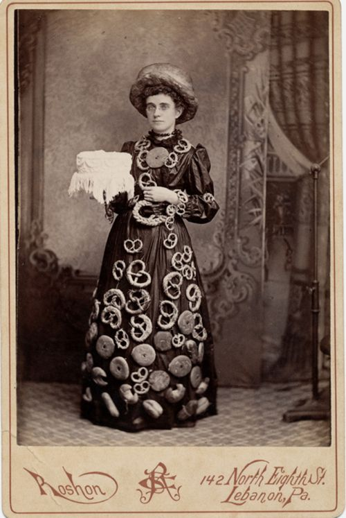 ca. 1870-1900, [cabinet card, portrait of a woman identified as Marie Stover of Williamsport, Pennsylvania, holding a cake and wearing a loaf of bread as a hat and a dress adorned with donuts and cookies, and pretzels. Presumably, she is advertising a bakery], Roshon