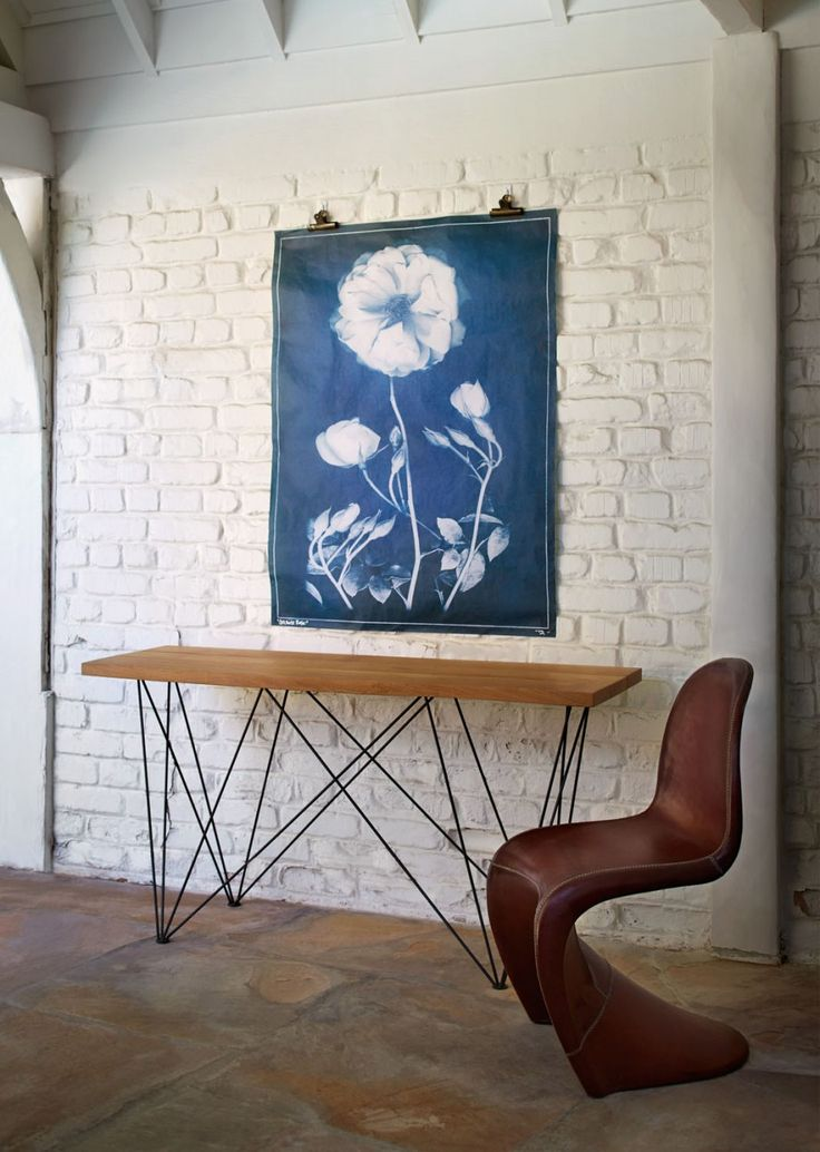 Console Table In Hallway With Modern Chair, Exposed Brick Wall Painted  White, And Oversized Artwork