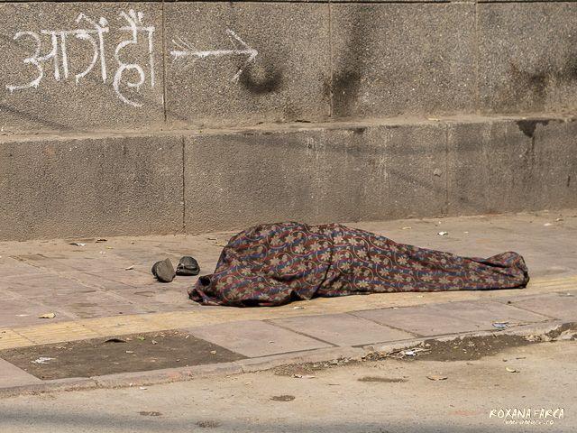 Doarme. Şi-a lăsat papucii la intrare. / Sleeping on the street in India
