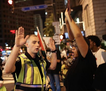 An Atlanta police officer tells Black Lives Matter protesters to move out of the street during a protest in downtown Atlanta, Saturday, Sept. 24, 2016. (AP Photo/Branden Camp)