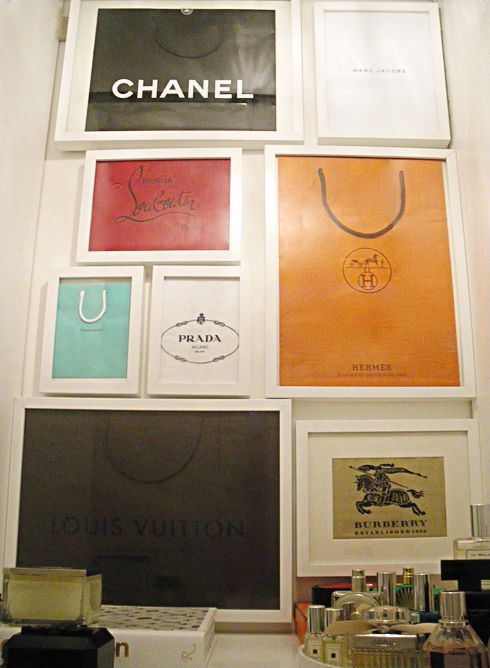 Lovely way to use designer shopping bags as decor in a closet. Frame them.