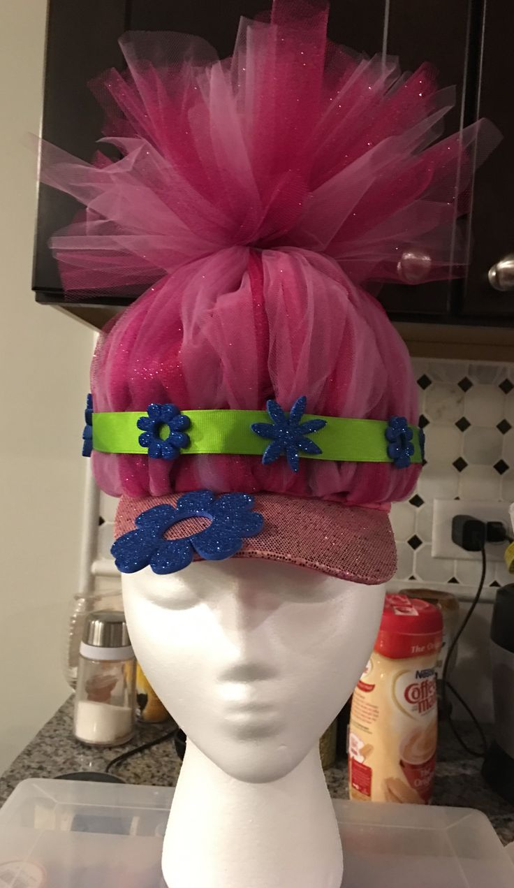 Made a troll hat for crazy hat/hair day at school.  Cut a piece of elastic long enough to go around an old hat then made a mini tulle tutu.  Tacked down the skirt to the hat using a thread and needle being sure to go through the elastic and hat material, tied the ends together with some yearn, and trimmed the top as needed.  Added the ribbon and foam flowers.  My PreK student loves it and it's so cute on!