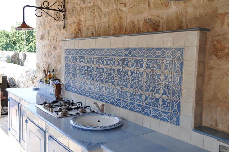 cucina in muratura con piastrelle in terracotta e top in pietra lavica con lavello in pietra lavica decorato