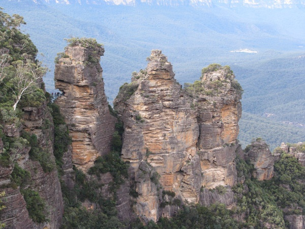 The Three Sisters are located in the Blue Mountains, west of Sydney, NSW. They are made up of sandstone, a sedimentary rock dating back to the Triassic (about 200 million years ago). Subsequent erosion has formed spectacular scenery such as the Three Sisters, Jamison Valley and Mt Solitary.