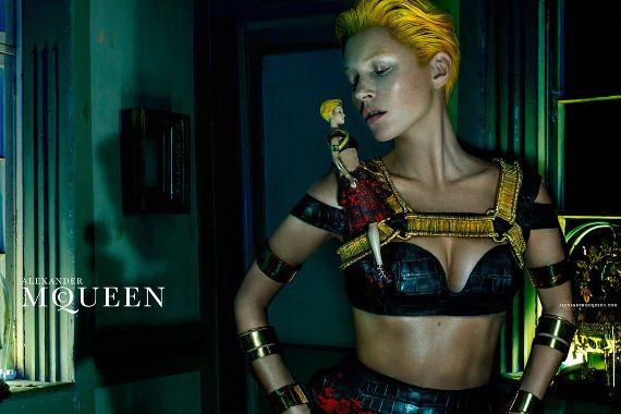 ALEXANDER MCQUEEN  Gdyby u McQueena było grzecznie i spokojnie oznaczałoby to, że świat się kończy, a cały świat mody może zwinąć manatki i spadać do domu. Wyjątkowo mroczna Kate Moss, dzierżąca w rękach voodoo barbie może nie przyprawia o palpitacje, ale wprowadza w thrillerowy klimat. Majaczące w tle maski opływają w ciemnościach. Nic nie płonie – poza czupryną Kate.  Więcej na Moda Cafe!