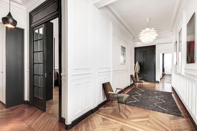 Dans le couloir, un enchevêtrement de cadres décorent les murs. Au fond, la partie enfant de l'appartement comporte deux chambres, une salle de bains et un dressing.