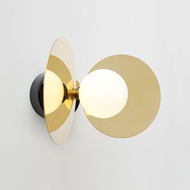 L'applique Ilios est réalisée en laiton massif, métal laqué époxy et verre opale. Le disque en laiton reflète la lumière du globe (