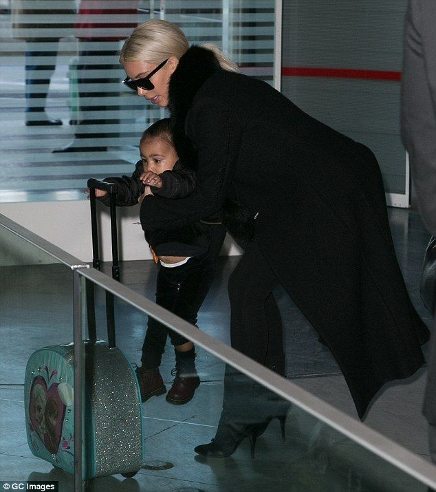A helping hand: Kim lifted North up as the pair went through airport security before their flight