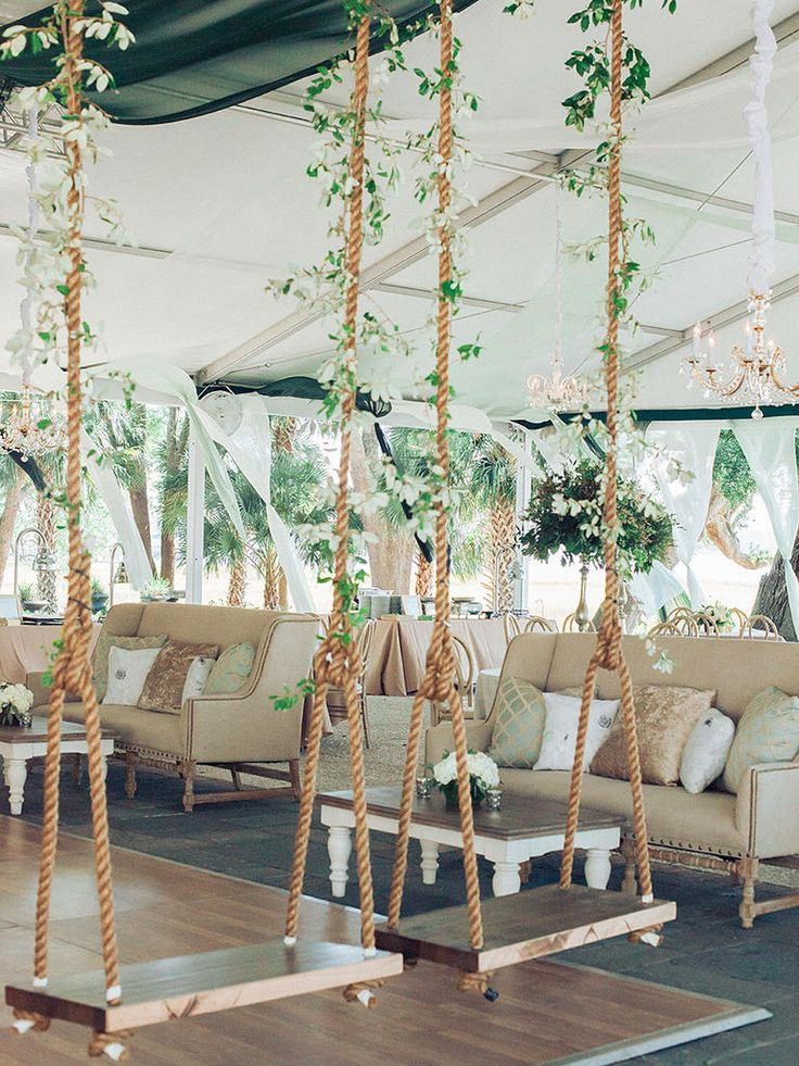 Channel the whimsy of a secret garden with floral wedding tent swings that make for stunning outdoor photo ops.