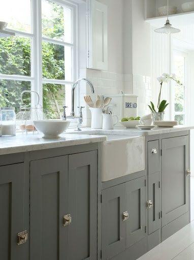 Une belle cuisine lumineuse, blanche et grise, avec des plans de travail en marbre.