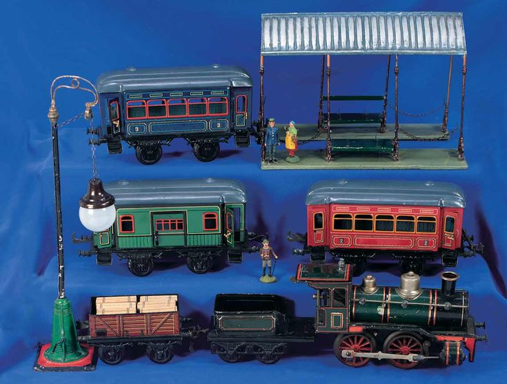 German tin train with accessories marked Märklin (caboose and green car) and Gebrüder Bing (red and coal cars). Early 20th century.