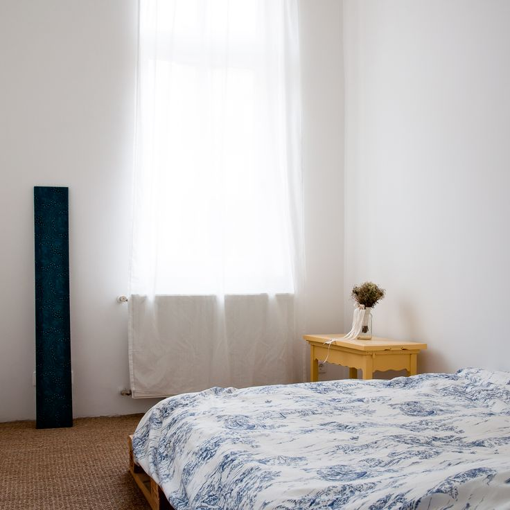minimalist bedroom with pallet bed and Australian art
