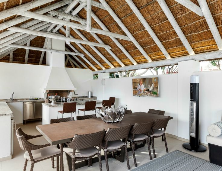 Modern outdoor living space with thatched roof, kitchen and dining area!
