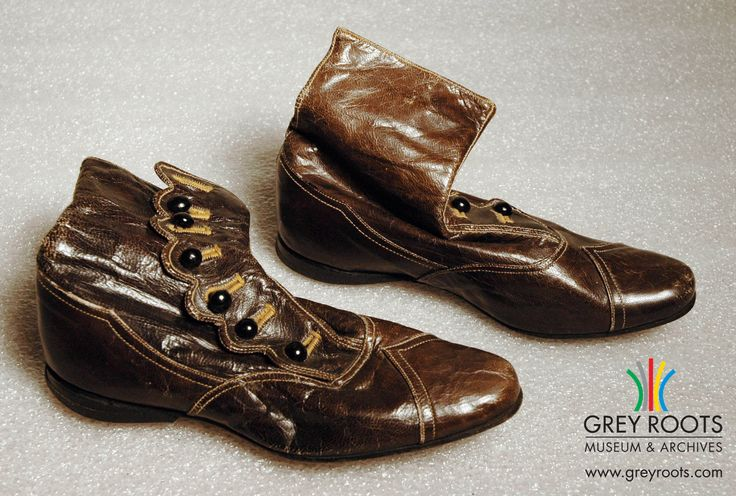 A pair of child's, brown leather, button-up boots. Each boot has seven black buttons which attach to the scalloped edge of the buttonhole flap. The boots have several seemed decorations. Grey Roots Museum & Archives Collection.