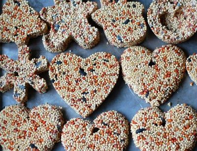 Bird Seed ORnaments  3/4 cup flour   1/2 cup water   1 envelope unflavored gelatin   3 tbsp. corn syrup   4 cups birdseed   molds (muffin tin, cookie cutters, etc.)   nonstick spray   drinking straw   waxed paper   ribbon/twin