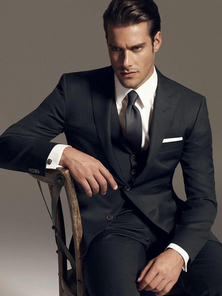 黒スーツ無地に白ポケットチーフ、ブラックタイを合わせた着こなし