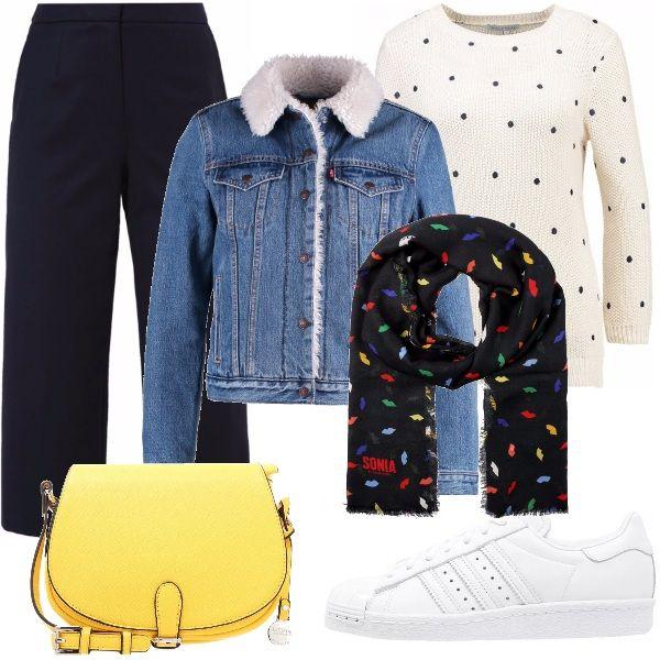 Un outfit comodo e sportivo. Pantaloni blu a vita alta, maglione bianco a pois blu, giubbino di jeans foderato con un caldo pellicciotto. Sciarpa multicolor con fondo blu, borsa a tracolla gialla e sneakers bianche.