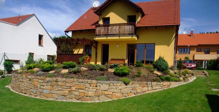 Bzovský pískovec z lomu Bzová. Zeď je postavená do oblouku složně ukládanými kameny, navazujícími schody sobrubou a cestičkou ze šlapáků.