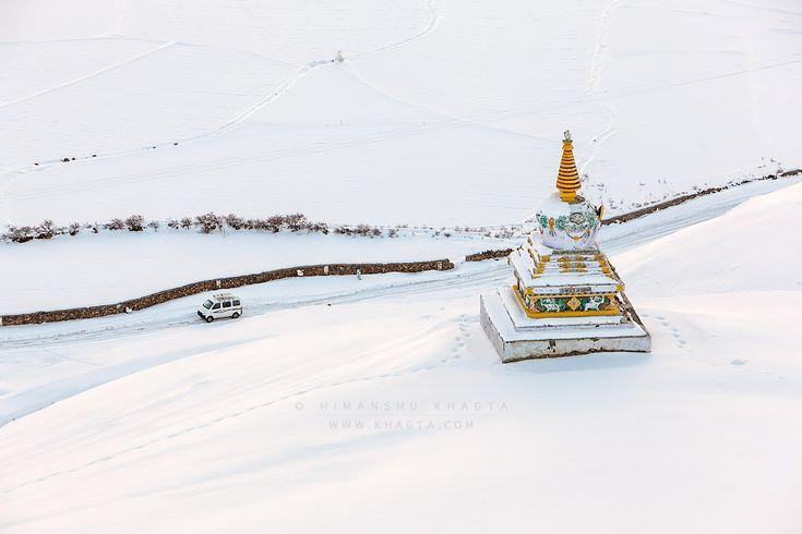 A car driving on snow covered road passes through a chorten near Rangrik village of Spiti