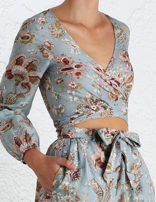 Pavilion Wrap Playsuit, from our Summer Swim 16 collection, in Floral printed silk cotton voile. Wrap playsuit, threads through belt loops to tie at front. Full length blouson sleeve with elastic cuff. Side pockets at hip, zip closure on shorts.