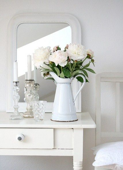 the flowers are so pretty and the white bedside table.