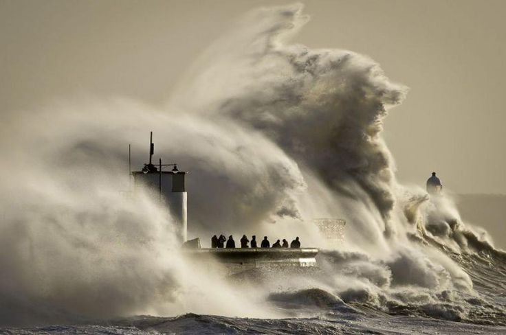 People watch and photograph enormous waves as they break on Porthcawl harbour