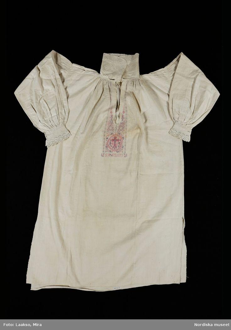 Mansskjorta,  brudgumsskjorta av vit halvlinnelärft, två bålstycken  och smala axelstycken.. Hög krage av bomullslärft avsedd att bäras uppstående, med 2,5 cm bred broderad bård i utdragssöm sk. stopphålsöm, kragen kantad med 3 cm bred knypplad spets.