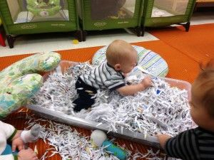 Infants playing with shredded paper