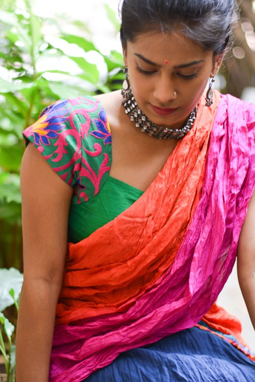 With a body of solid green and armbands and sleeves with twines & lotuses. This blouse feels field fresh without being overtly bold FABRIC: Body - Green raw silk Armband: Green dupion with yellow, pink and violet threadwork CARE: Dryclean only