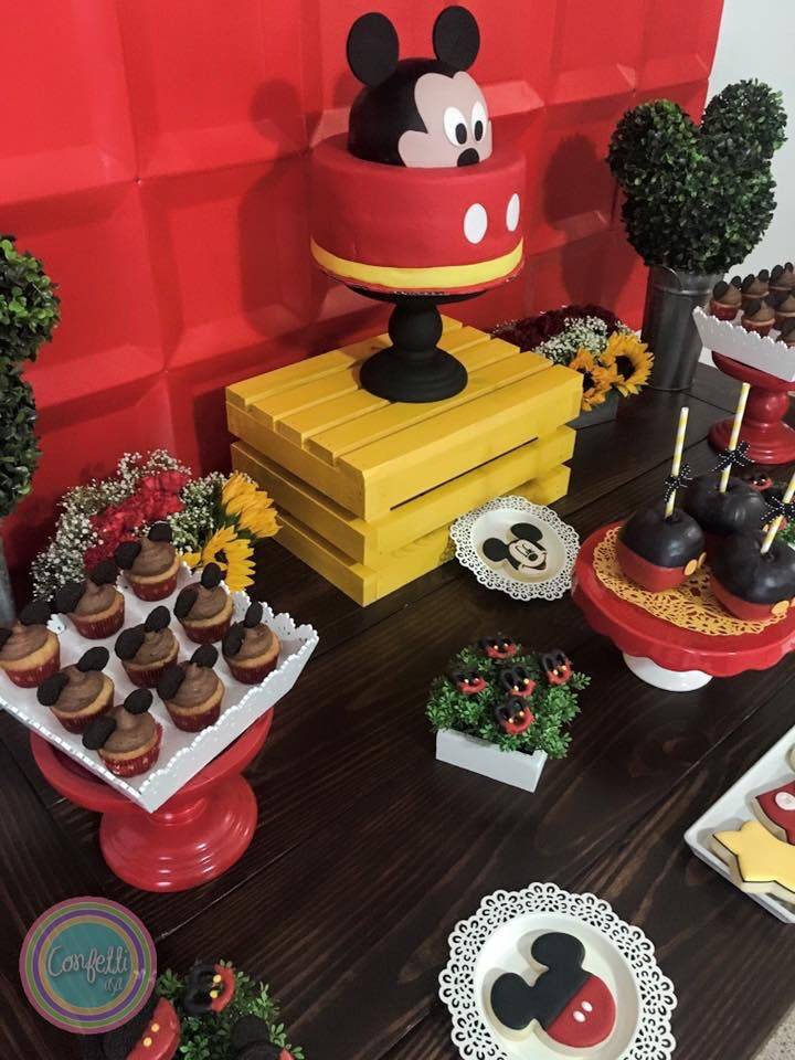 Mickey Mouse tablescape with banner and backdrop fondant cake sugar decorated cookies mini cupcakes dipped Oreos and dipped pretzels and chocolate dipped apples