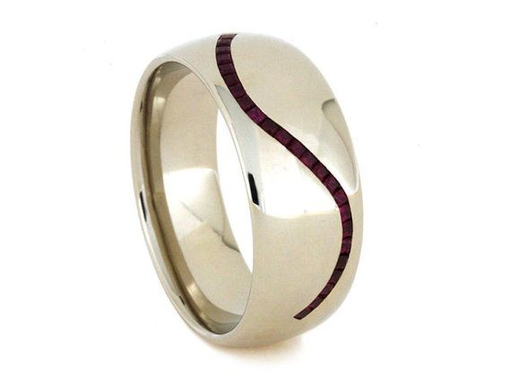 RING LAYOUT Ring Width: 10 mm tapered to 8 mm Ring Sleeve: 14k White Gold Ring Profile; Round Ring Finish: Polished Curved Partial Eternity inlay of Rubies Stone: Ruby (Qty: 24) Shape/Size: Princess Cut, 1.25 mm Quality: Genuine, AA Setting: Channel SKU: 3352 Available Ring Sizes: