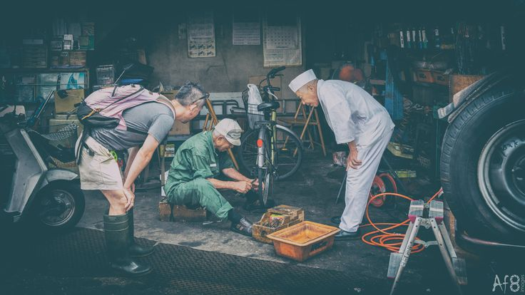 Many hands or too many cooks? - Onlookers provide advice to a mechanic in his workshop.