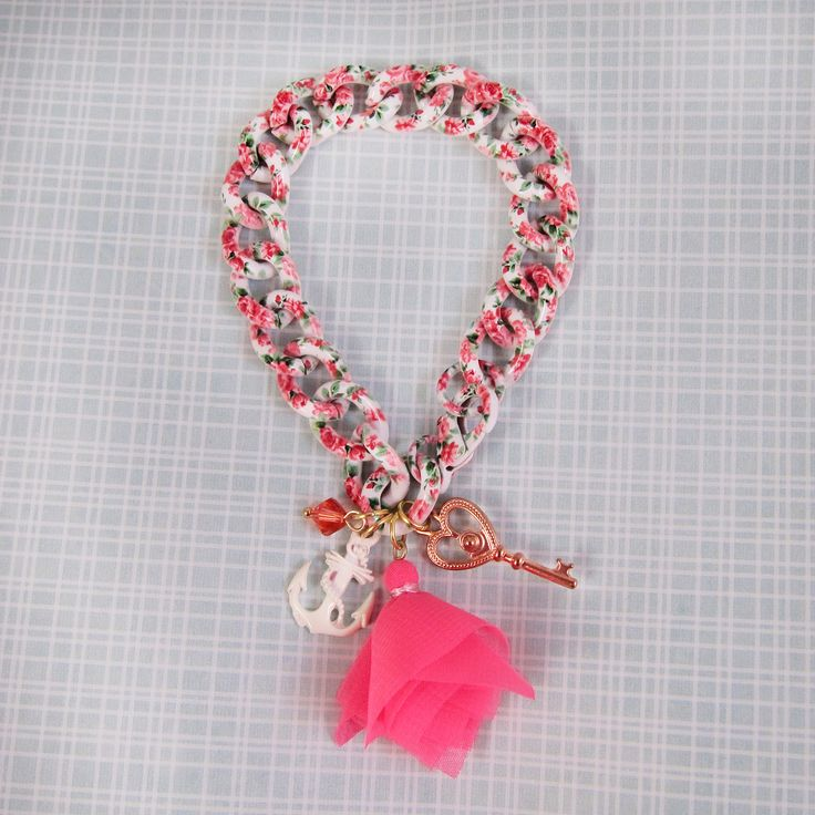 Floral print chain gives the bracelet an interesting and appealing, whimsical look. Very girly even with the chunky chain.  The floral print chain is country-girl-pleasing white with pink and magenta flowers and green leaves. Reminiscent of vintage patterns, it fits well for spring and summer. The charm dangles include a rose gold heart shaped filigree key, white anchor, neon pink chiffon tassel, and a single coral colored Swarovski crystal.