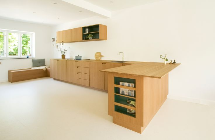 Spacious bespoke kitchen with strong lines in the composition and all surfaces miter jointed, giving this genuine oak wood kitchen an altogether airy expression.
