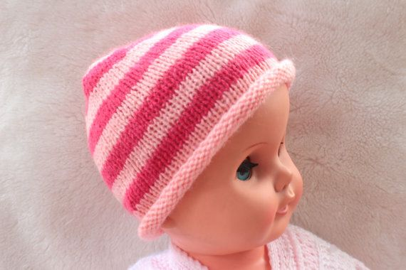 Pink wool mix hand knitted baby girl striped hat. This is a simple pull on hat with a roll-over brim in a soft wool mix. Suitable for a baby from