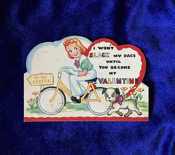 1930s bicycle girl in slacks & dog valentine die cut card. Made by Carrington Company, Chicago, Il. Has a more old fashioned verse on the back. In excellent condition. It is hard to believe this card is over 80 years old! Nice and flat with sharp edges. Colors are bright. Signed on