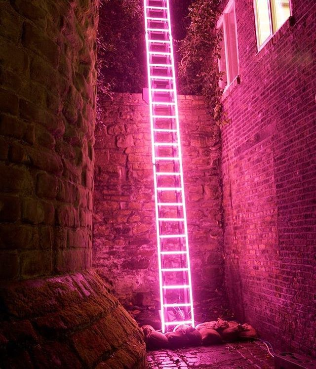 a neon pink ladder climbs up the stone wall offering a fantasy escape route… 'eschelle' by ron haselden. . . . more #art on #designboom! #ronhaselden #neonlights